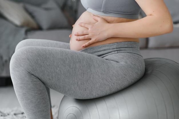Jovem mulher grávida fazendo ioga com bola fit em casa. conceito de gravidez de esportes saudáveis