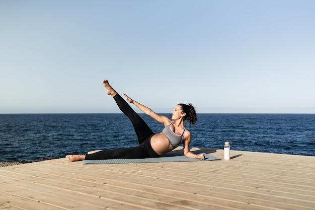 Jovem mulher grávida fazendo uma rotina de exercícios de ioga ao ar livre - foco no rosto