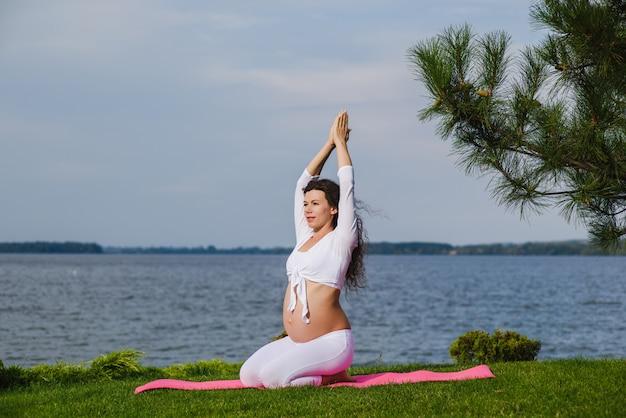 Jovem mulher grávida fazendo yoga ao ar livre