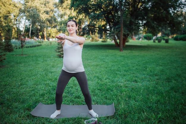 Jovem mulher grávida ficar no companheiro de ioga fora no parque. ela estica os braços e olha para a frente. modelo parece concentrado.