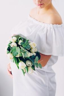 Jovem mulher grávida linda em um vestido branco com um buquê de tulipas brancas