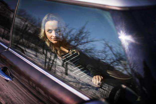 Jovem mulher grávida olhando pela janela do carro transparente