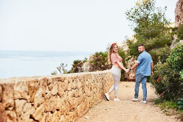 Jovem mulher grávida posando com o marido com vista para o mar
