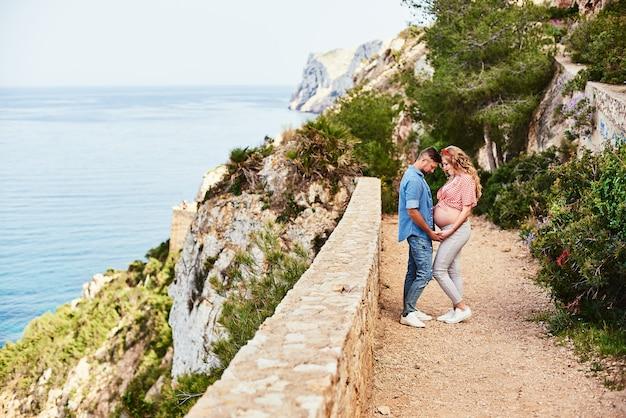 Jovem mulher grávida posando com o marido contra vista para o mar