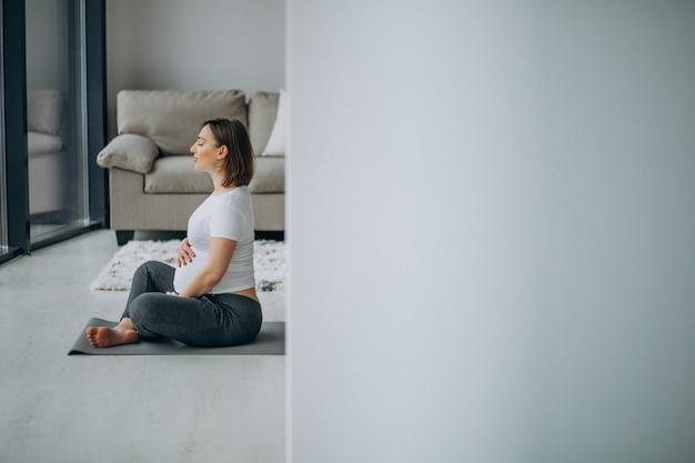 Jovem mulher grávida praticando ioga em casa