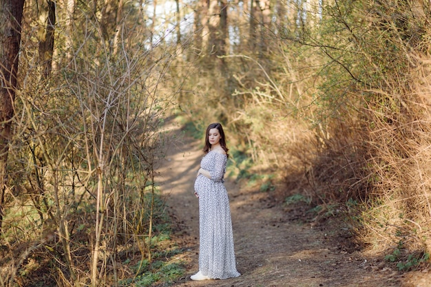Jovem mulher grávida relaxante no parque ao ar livre
