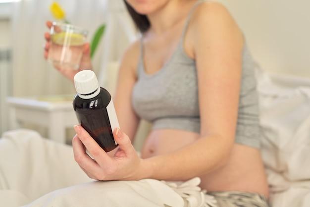 Jovem mulher grávida segurando o remédio solúvel na mão, vitaminas. mulher sentada em casa na cama