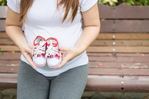 Jovem, mulher grávida, segurando, sapatos bebê, para, dela, barriga