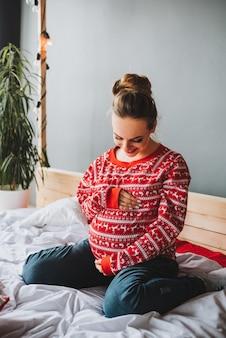 Jovem mulher grávida sentada numa cama olhando e batendo na barriga