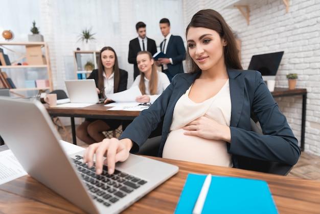 Jovem mulher grávida trabalhando dentro do escritório