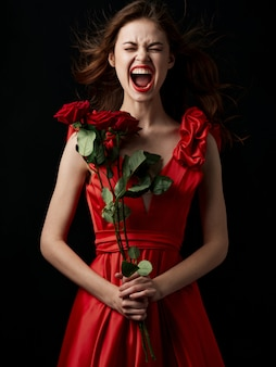Jovem mulher gritando com rosas vermelhas nas mãos em um vestido vermelho
