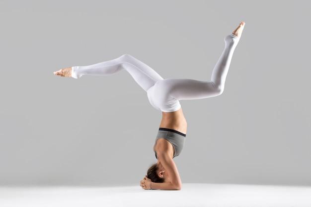 Jovem, mulher, headstand, pose, cinzento, estúdio, fundo