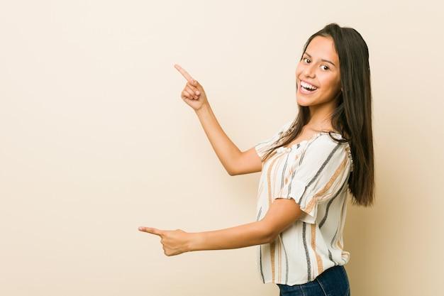 Jovem mulher hispânica animado apontando com o dedo indicador fora.