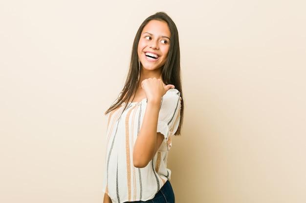 Jovem mulher hispânica aponta com o dedo polegar, rindo e despreocupado.