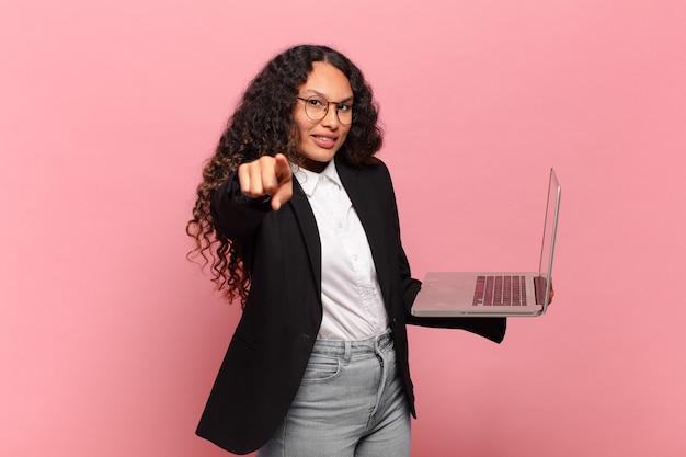 Jovem mulher hispânica, apontando para a câmera com um sorriso satisfeito, confiante e amigável, escolhendo você. conceito de laptop