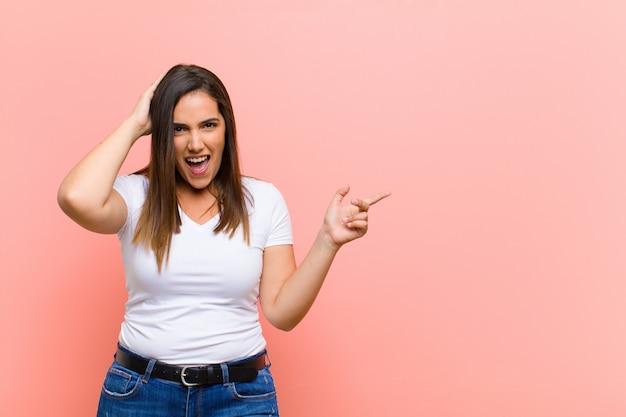 Jovem mulher hispânica bonita rindo, parecendo feliz, positiva e surpresa, percebendo uma ótima idéia apontando para o espaço lateral da cópia contra a parede rosa