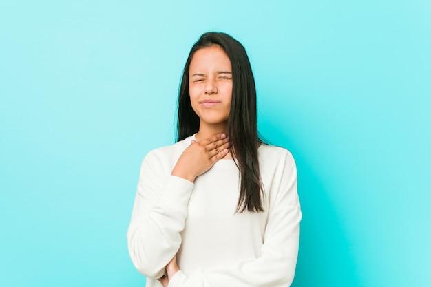 Jovem mulher hispânica bonita sofre de dor na garganta devido a um vírus ou infecção.