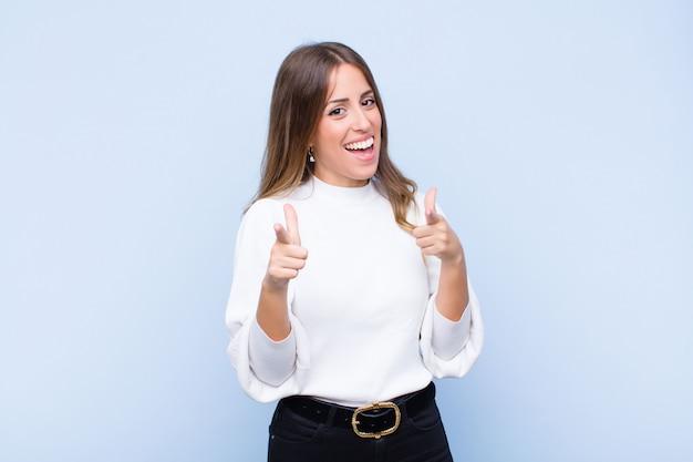 Jovem mulher hispânica bonita sorrindo com uma atitude positiva, bem sucedida e feliz apontando, fazendo sinal de arma com as mãos contra a parede azul