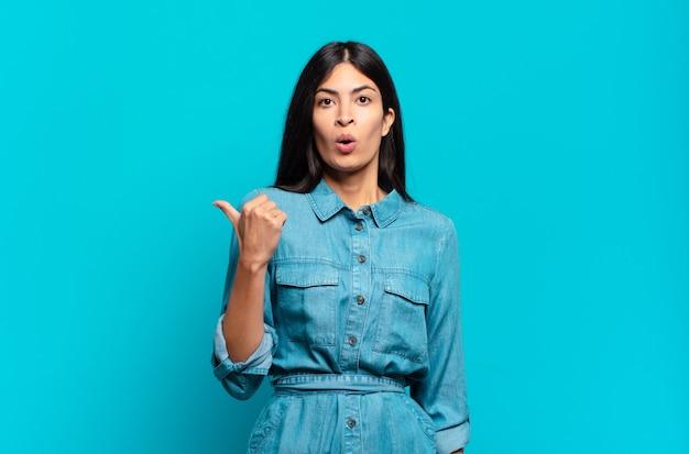 Jovem mulher hispânica casual parecendo espantada com a descrença, apontando para um objeto ao lado e dizendo uau, inacreditável