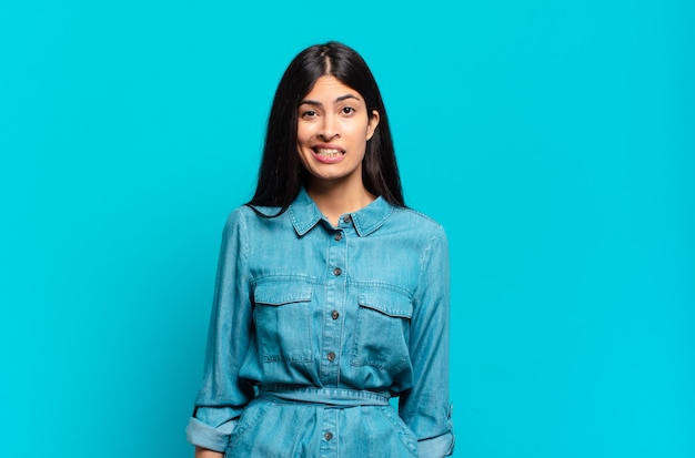 Jovem mulher hispânica casual parecendo perplexa e confusa, mordendo o lábio com um gesto nervoso, sem saber a resposta para o problema