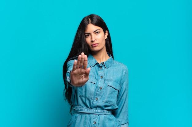 Jovem mulher hispânica casual parecendo séria, severa, descontente e irritada, mostrando a palma da mão aberta fazendo gesto de pare