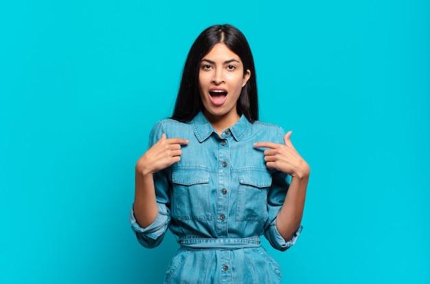 Jovem mulher hispânica casual se sentindo feliz, surpresa e orgulhosa, apontando para si mesma com um olhar animado e surpreso