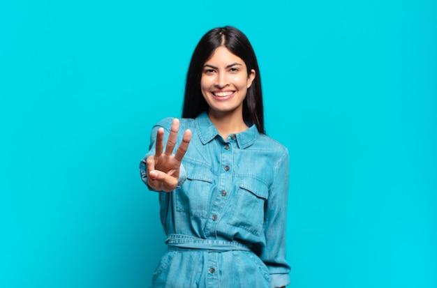 Jovem mulher hispânica casual sorrindo e parecendo amigável, mostrando o número três ou terceiro com a mão para a frente, em contagem regressiva