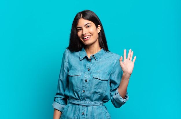 Jovem mulher hispânica casual sorrindo feliz e alegre, acenando com a mão, dando as boas-vindas e cumprimentando você ou dizendo adeus