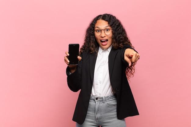 Jovem mulher hispânica. choque ou surpresa. apontando gesto de negócios e conceito de smartphone