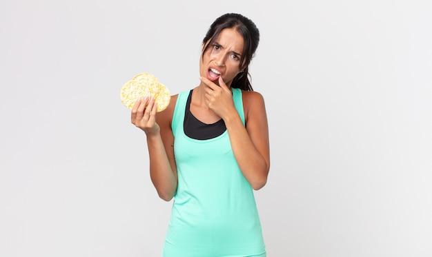 Jovem mulher hispânica com a boca e os olhos bem abertos e a mão no queixo. conceito de dieta de fitness