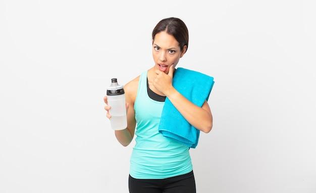 Jovem mulher hispânica com a boca e os olhos bem abertos e a mão no queixo. conceito de fitness