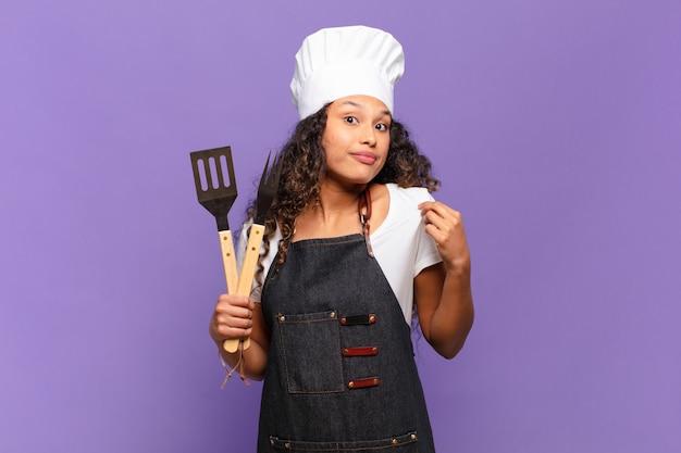 Jovem mulher hispânica com aparência arrogante, bem-sucedida, positiva e orgulhosa, apontando para si mesma. conceito de chef de churrasco