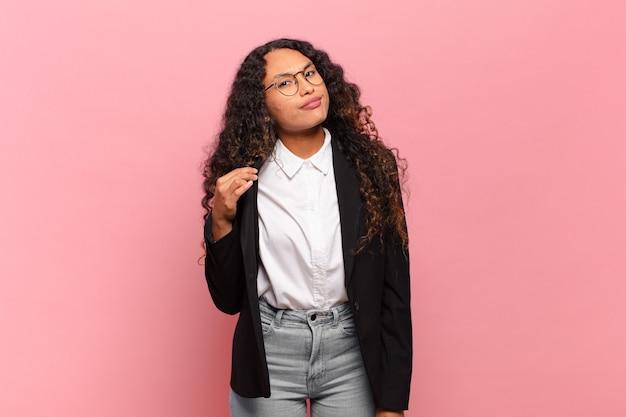 Jovem mulher hispânica com aparência arrogante, bem-sucedida, positiva e orgulhosa, apontando para si mesma. conceito de negócios