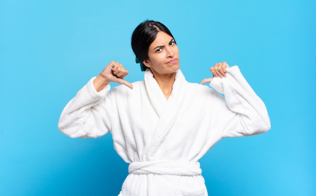Jovem mulher hispânica com aparência triste, decepcionada ou com raiva, mostrando os polegares para baixo em desacordo, sentindo-se frustrada. conceito de roupão de banho