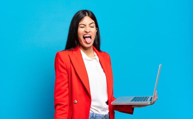 Jovem mulher hispânica com atitude alegre, despreocupada, rebelde, brincando e mostrando a língua, se divertindo. conceito de laptop