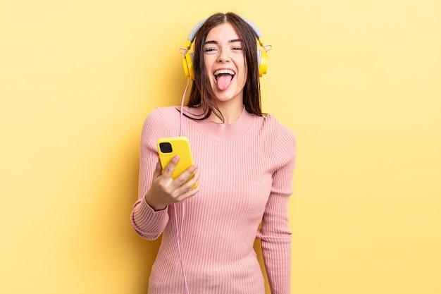 Jovem mulher hispânica com atitude alegre e rebelde, brincando e mostrando a língua. fones de ouvido e conceito de telefone