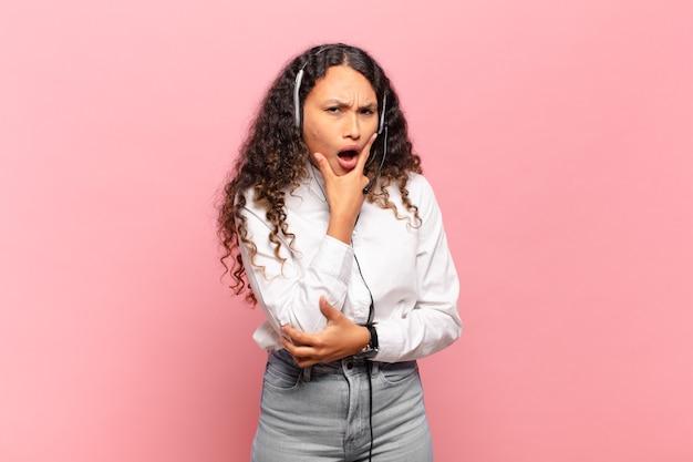 Jovem mulher hispânica com boca e olhos bem abertos e mão no queixo, sentindo-se desagradavelmente chocada, dizendo o quê ou uau. conceito de telemarketing