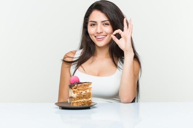 Jovem mulher hispânica, comendo um bolo alegre e confiante mostrando okey gesto