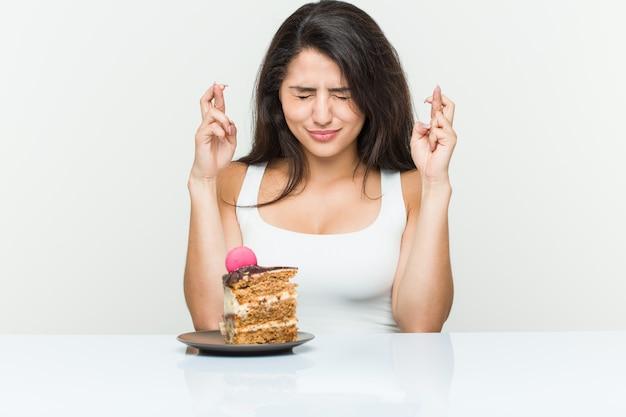 Jovem mulher hispânica, comendo um bolo cruzando os dedos por ter sorte