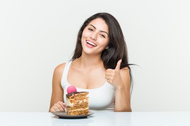 Jovem mulher hispânica, comendo um bolo, sorrindo e levantando o polegar