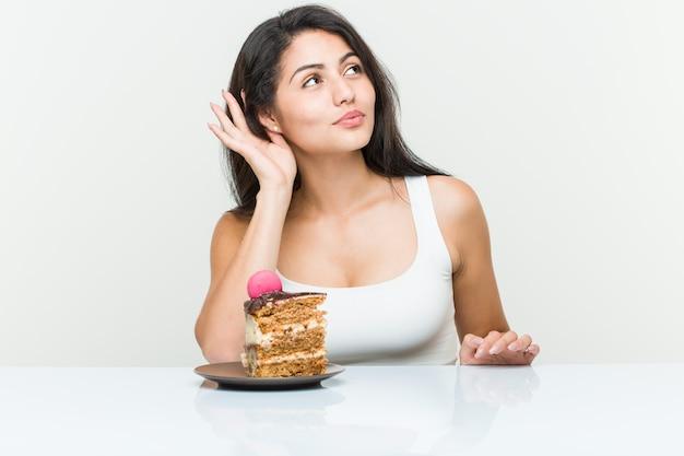 Jovem mulher hispânica, comendo um bolo, tentando ouvir uma fofoca.