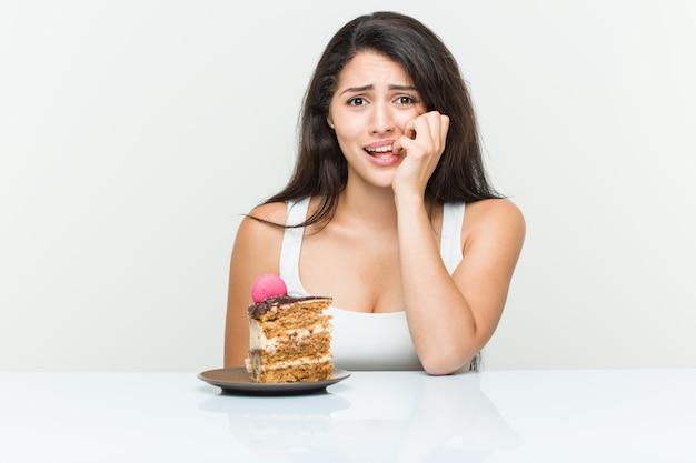 Jovem mulher hispânica, comer um bolo de roer as unhas, nervoso e muito ansioso.