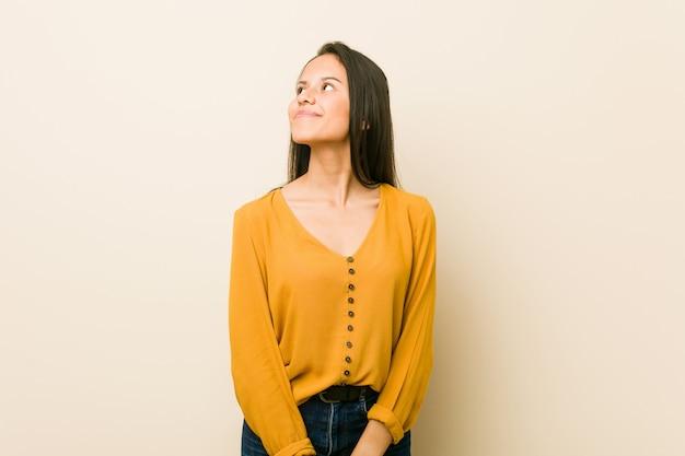 Jovem mulher hispânica contra bege sonhando em alcançar objetivos