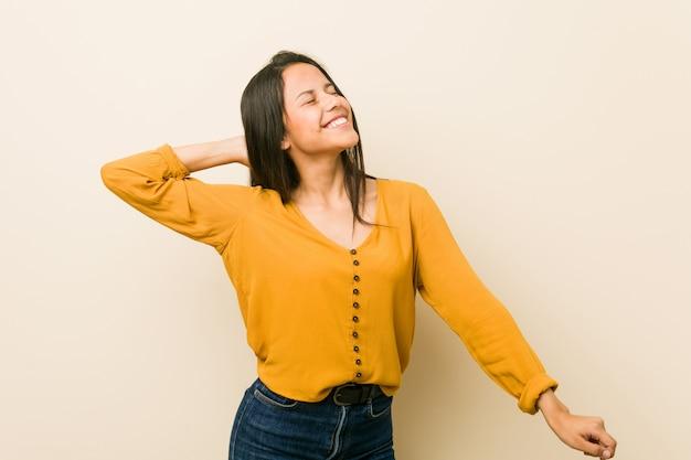 Jovem mulher hispânica contra uma parede bege dançando e se divertindo.
