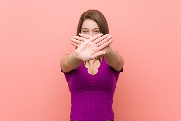 Jovem mulher hispânica contra uma parede rosa, fazendo um gesto de negação