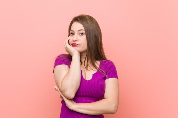 Jovem mulher hispânica contra uma parede rosa que está entediada, cansada e precisa de um dia de relaxamento.