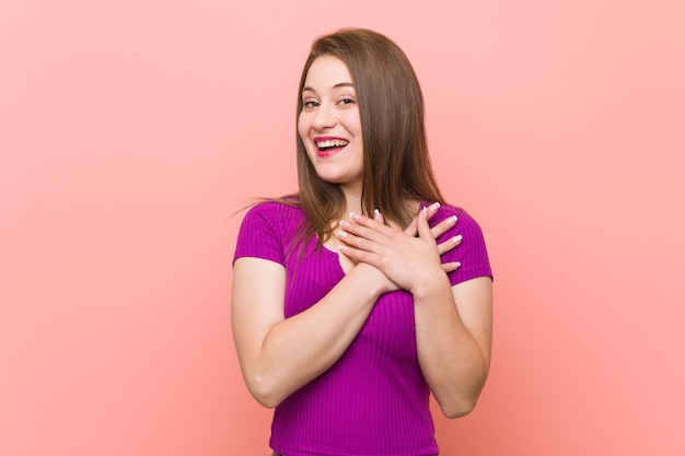 Jovem mulher hispânica contra uma parede rosa tem uma expressão amigável, pressionando a palma da mão no peito