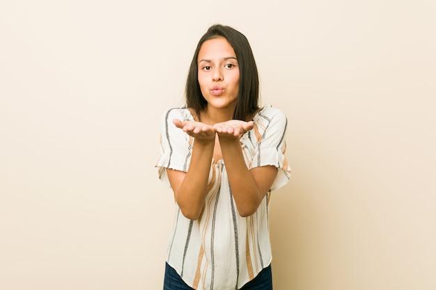 Jovem mulher hispânica, dobrar os lábios e segurando as palmas das mãos para enviar beijo de ar.