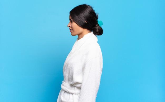 Jovem mulher hispânica em vista de perfil, olhando para copiar o espaço à frente, pensando, imaginando ou sonhando acordado. conceito de roupão de banho