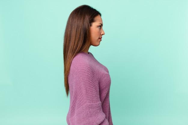 Jovem mulher hispânica em vista de perfil, pensando, imaginando ou sonhando acordada